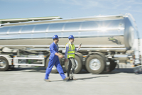 Businessman and worker walking along stainless steel milk tanker