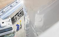 Workers talking next to stainless steel milk tanker 11086013341| 写真素材・ストックフォト・画像・イラスト素材|アマナイメージズ