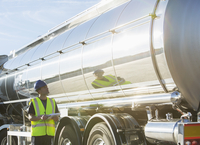 Worker with clipboard checking stainless steel milk tanker