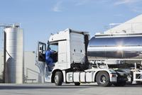 Truck driver climbing into stainless steel milk tanker 11086013363| 写真素材・ストックフォト・画像・イラスト素材|アマナイメージズ