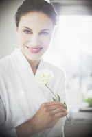 Portrait of smiling woman in bathrobe holding white rose