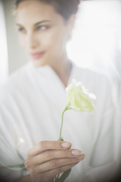 Close up of woman in bathrobe holding white rose