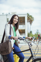 Portrait of smiling casual businesswoman on bicycle on urban street