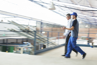 Supervisor and worker walking in food processing plant