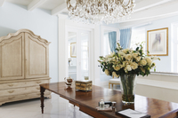 Chandelier over rose bouquet on table in luxury foyer