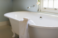 Bar soap and towel on ledge of claw foot tub
