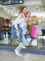 Man carrying girlfriend piggyback in shopping mall