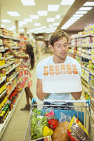 Man examining carton of eggs in grocery store