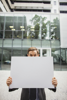 Businessman holding cardboard outside of office building