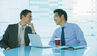 Businessmen talking at table in office building