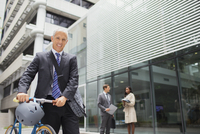 Businessman walking bicycle outside of office building