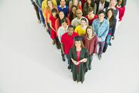 Diverse crowd behind confident graduate 11086017344| 写真素材・ストックフォト・画像・イラスト素材|アマナイメージズ