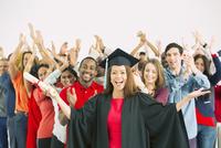 Crowd cheering behind confident graduate 11086017369| 写真素材・ストックフォト・画像・イラスト素材|アマナイメージズ