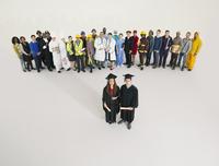 Portrait of graduates with workers in background 11086017399| 写真素材・ストックフォト・画像・イラスト素材|アマナイメージズ