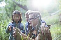Students and teacher examining grass in forest 11086017922| 写真素材・ストックフォト・画像・イラスト素材|アマナイメージズ