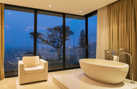 View of luxurious bathroom with bathtub and armchair at night