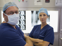 Portrait of surgeons with arms crossed, standing in front of MRI scan and x-ray