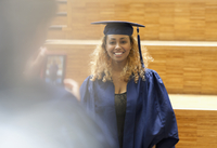 Female student in graduation gown posing for picture in university corridor