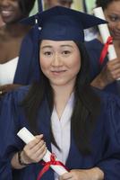 Female student smiling at camera and holding diploma 11086019816| 写真素材・ストックフォト・画像・イラスト素材|アマナイメージズ