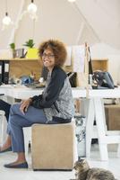 Young smiling woman sitting at desk 11086020239| 写真素材・ストックフォト・画像・イラスト素材|アマナイメージズ