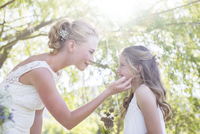 Bride and bridesmaid facing each other in domestic garden during wedding reception 11086020712| 写真素材・ストックフォト・画像・イラスト素材|アマナイメージズ