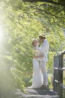 Young couple embracing on wooden bridge 11086020715  写真素材・ストックフォト・画像・イラスト素材 アマナイメージズ