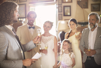 Best man toasting with champagne and giving speech during wedding reception in domestic room
