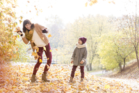 Playful mother and daughter throwing leaves in autumn park