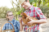 Father and daughter petting chicken