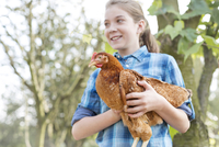Smiling girl holding chicken