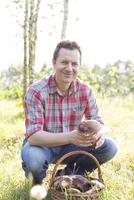 Portrait of smiling man harvesting mushrooms in field