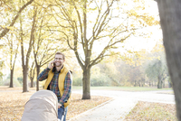 Smiling father talking on cell phone and pushing stroller in sunny autumn park