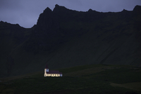 Illuminated church below cliffs, Vik, Iceland