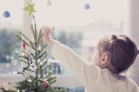 Girl reaching for start on Christmas tree