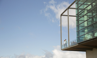 Men standing on balcony of glass bump out against blue sky