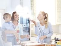 Woman blowing flour baking in kitchen