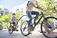 Son in helmet riding tandem bicycle with mother in urban park 11086022505| 写真素材・ストックフォト・画像・イラスト素材|アマナイメージズ