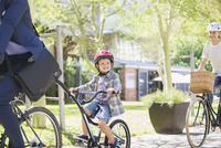 Portrait smiling boy in helmet riding tandem bicycle with father in park 11086022512| 写真素材・ストックフォト・画像・イラスト素材|アマナイメージズ