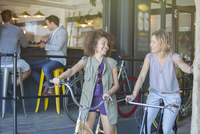 Smiling women on bicycles outside cafe patio 11086022526| 写真素材・ストックフォト・画像・イラスト素材|アマナイメージズ