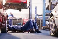 Mechanic under car in auto repair shop 11086022781| 写真素材・ストックフォト・画像・イラスト素材|アマナイメージズ