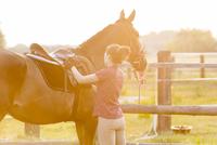 Woman preparing saddle for horseback riding in rural pasture 11086023084| 写真素材・ストックフォト・画像・イラスト素材|アマナイメージズ