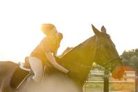 Woman on horseback petting horse in rural pasture 11086023105| 写真素材・ストックフォト・画像・イラスト素材|アマナイメージズ