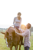 Smiling couple horseback riding in rural pasture