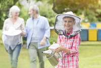 Portrait smiling boy in beekeeper hat holding smoker