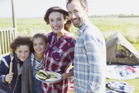 Portrait smiling family with barbecued hamburgers at sunny campsite