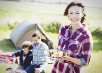 Portrait smiling woman with vegetable skewers at sunny campsite