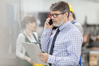 Businessman with clipboard talking on cell phone in factory
