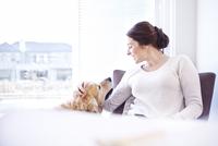 Woman petting dog at window