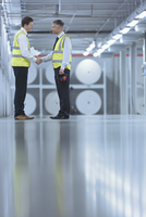 Businessmen in reflective clothing shaking hands in printing plant