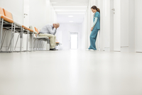Stressed doctor and nurse in hospital corridor